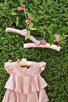 Pink, ruffled dress and romantic coat hangers with crocheted flowers hanging from rose branch in box hedge