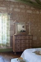 Two table lamps and mirror on top of antique chest of drawers in Mediterranean bedroom with stone walls