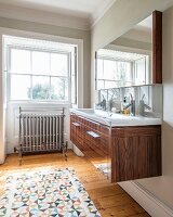 Wooden washstand, patterned rug on wooden floor and deep-set window in background