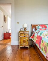 Oriental cabinet next to antique bed with patchwork quilt next to open door with view of red-painted trunk