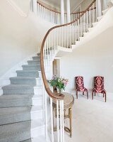 Curved staircase with pale grey runner and chairs with patterned upholstery in elegant foyer