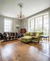 Velvet sofas on wooden floor and large, arched window in spacious living room