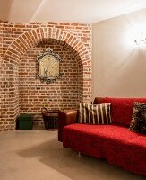 Red throw on sofa in cellar-like room with arched niche in brick wall