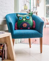 Owl-shaped cushion on blue fifties' armchair
