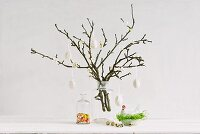 Easter arrangement of spring branches with blossom buds decorated with white hens' eggs