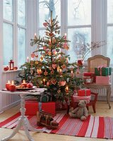 Classic Christmas tree decorated in red and white with gingerbread and fabric baubles and candles in conservatory