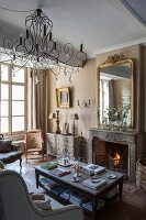 Antique furniture and seating area in front of open fireplace with marble surround