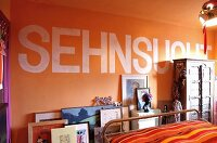 Detail of bedroom with motto on orange wall
