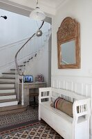 Decorative mosaic tiled floor and foot of winding staircase in hallway
