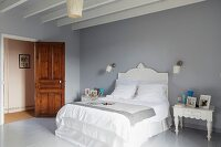 White bed in French bedroom with dove-grey wooden floor and walls
