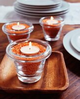 Glass tealight holders filled with red lentils and lit candles
