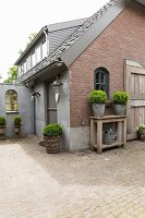 Planters on wooden table against brick gable-end wall and paved courtyard outside house with dormer windows