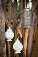 Ethnic lanterns made from wire and perforated, white metal hanging from branches
