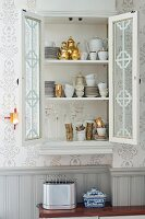 Crockery cabinet with open door built into niche