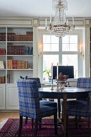 Tartan upholstered chairs at round table below antique chandelier in front of bookcases