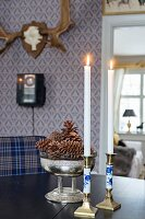 Candlesticks and antique silver bowl of pine cones on table in front of hunting trophy on blue wallpaper