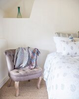 Antique, rustic-style easy chair next to bed below delicate vase in corner niche