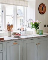 Kitchen counter with stone worksurface and country-house-style base units painted pale grey below window