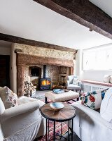 Side table between comfortable armchairs and log-burner in old fireplace in living room
