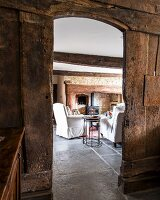 Open doorway in rustic board wall leading to comfortable white armchairs in front of fireplace