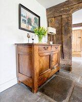 Vase of tulips on simple, wooden cabinet on old stone floor in front of open doorway in rustic board wall