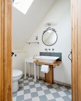Custom wooden washstand with countertop sink and white and pale grey chequered floor tiles in bathroom seen through open door