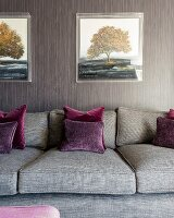 Grey sofa, dark red scatter cushions and grey and brown striped wallpaper