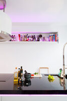 Kitchen utensils on black polished worksurface of island counter opposite wall-mounted shelf illuminated by purple light