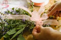 Tying bouquet of herbs with a ribbon