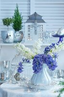 Christmas arrangement of purple and white hyacinths, ornamental bird cage and mercury silver vases