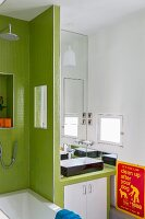 Washstand with base unit next to partition wall covered in green mosaic tiles
