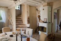 Dining area in front of winding staircase and fireplace in open-plan interior of country house