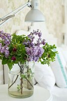 Bouquet of lilac and wild roses in simple glass vase