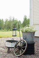Arrangement of zinc buckets, cartwheel and lantern in garden