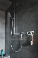 A grey-tiled shower cabin with taps and a hand-held shower head in a holder