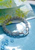 A beaded bracelet with a knitted encasing with blue beads next to it