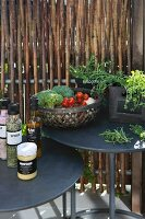 Spices, herbs and vegetables on two round, black side tables