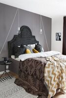 Textiles with various patterns on bed with upholstered headboard