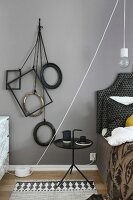 Various frames hanging from cords on wall next to bed