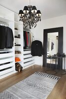 Open-fronted wardrobes, black chandelier and full-length mirror in dressing room