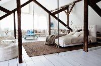 Bedroom in open-plan attic interior with exposed beams