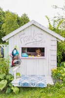 Little girl playing in wooden play house with window in gable end in summery garden