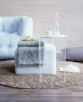 Woollen blanket on pouffe and delicate side table on woollen rug