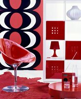 Retro living area with red shell chair and white shelving unit with open fronts and red and white fronts
