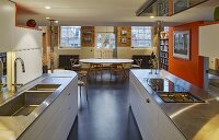 Open-plan kitchen with orange partition wall and black floor