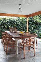 Classic chairs around rustic dining table on roofed terrace