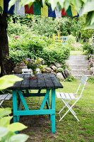 Rustic garden table with turquoise-painted frame and folding chairs in front of steps in garden
