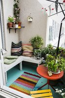 Cushions on wooden bench and potted plants on balcony