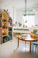 Toys on round wooden table on white wooden floor, house-shaped shelving units and white bed below window in child's bedroom