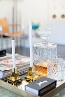 White candles in brass candlesticks next to crystal carafe and glasses on tray